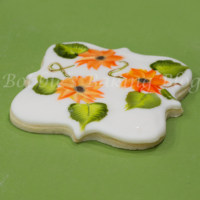 Learn how hand paint sunflowers on a sugar cookie: step by step video